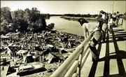 "People stand on the southbound span of the Kansas River Bridge to observe the makeshift village ""Tent City"" during the filming of the movie ""The Day After"" in September of 1982."