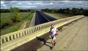 Mark Henderson, of Pearland, Texas, runs alone as he crosses over the Kansas Turnpike near Cassoday. Henderson finished first among 43 runners who participated this past month in the Heartland 100-Mile Run through the Kansas Flint Hills.