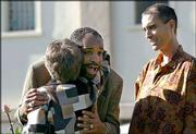 Clare Bouquet, left, hugs Jim Jones Jr. as Stephan Jones, right, watches during a service on the 25th anniversary of the Jonestown tragedy. The memorial was Tuesday at Evergreen Cemetery in Oakland, Calif., where more than 400 victims of the mass suicide are buried. The Joneses are sons of Jim Jones of the Peoples Temple.