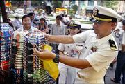 Ensign Mary Alcantara, 23, from Northridge, Calif., center, and Lt. j.g. Don Shrader, 31, right, from San Diego, shop for souvenirs in Ho Chi Minh City, formerly Saigon, Vietnam. The two naval officers are from the USS Vandegrift, which on Wednesday became the first US. Navy ship to dock in Ho Chi Minh City since the end of the Vietnam War.