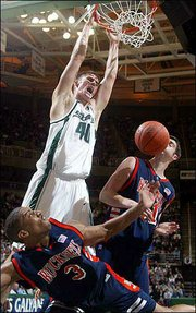 Michigan State's Paul Davis (40) dunks over Bucknell's Charles Lee (3) and Chris Niesz. The Spartans beat the Bison, 64-52, Friday in East Lansing, Mich.
