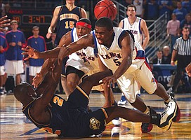 Kansas University's Keith Langford (5) dives for the ball and teammate J.R. Giddens closes in as Tennessee-Chattanooga's Casey Long hits the deck in the Jayhawks' 90-76 victory. KU opened its season with a victory Friday at Allen Fieldhouse.