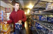 Parkway Wine and Spirits employee Brett Emert stocks beer in the cooler. Despite selling liquor on Sundays, some Lawrence liquor store owners say they haven't seen a significant increase in sales.