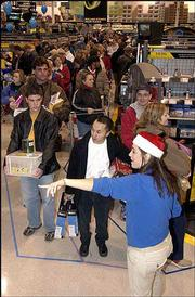 The lines were long at Best Buy as customers arrived early to scoop up special deals. Employee Becca Hinckley, bottom right, helped direct holiday shoppers to checkout lanes Friday at the store at 31st and Iowa streets. Lawrence shoppers joined millions of others nationwide for one of the busiest shopping days of the year.