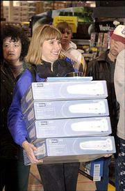 Lisa Gay, of Lawrence, cashed in on some deals at Best Buy and loaded up on DVD players. In a post-Thanksgiving tradition, bargain hunters were out in droves early Friday to begin their Christmas shopping.