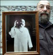 Charles Gruber, an initiated Sufi, poses with a photo of Hazrat Inayat Khan, who brought Sufism to the West.