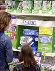 "Carolyn Schnell and daughter, Avery, 7, of Robbinsville, N.J., look at Leapster items at the Toys ""R"" Us store in Lawrenceville, N.J. Wal-Mart Stores Inc. and Toys ""R"" Us Inc. are engaged in a high-stakes battle for market share."