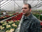John Clark, owner of Summerfield Greenhouse in Springfield, Mo., stands among some of the thousands of poinsettias that line his shelves. Churches, businesses and individuals buy $200 million of poinsettias annually in the United States.