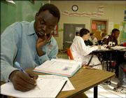 Tong Athwai, 16, studies during his Intro to Algebra class at the Highland Park Success Academy in Topeka. Athwai, a refugee from Sudan, has found a new home in Topeka.