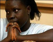 Helen Akut, 20, listens to questions about her family's move from Sudan to the United States during an interview in Topeka.