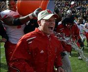 Nebraska football coach Frank Solich is doused by Brandon Teamer, left, after NU's 31-22 victory over Colorado. The Huskers won the game Friday in Boulder, Colo., but Solich was fired Saturday.