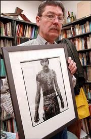 Kansas University anthropology professor Don Stull and a partner have spent years writing a book on the nation's meatpacking industry. Wednesday at his office at KU, Stull held a photo by Richard Avedon of Blue Cloud Wright, a slaughterhouse worker in Omaha, Neb.