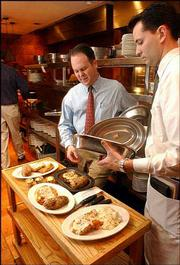 Doug Holiday, left, general manager of Hereford House in Lawrence, chats with server Brad Axon in November 2002. The restaurant recently raised its prices due to the high cost of beef.