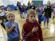 Woodlawn School students Ryan Armstrong, left, and Connor Ballenger, center, recite the Pledge of Allegiance. The students said the pledge in October in the school gym.