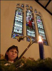 Molly Olson-Kelly, 10, lights a candle on an Advent wreath at Trinity Lutheran Church, 1245 N.H. Many churches in Lawrence light candles on wreaths to celebrate Advent in preparation for Christmas.