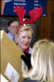 Postal clerk Tammy Rattenne adds some levity to the holiday mail rush with a pair of red reindeer antlers. Rattenne manned the counter Friday at the main post office on Seventh and Vermont streets.