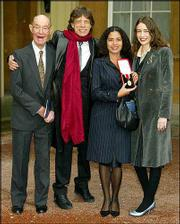 Rolling Stone Sir Mick Jagger, 60, with his 92-year-old father, Joe, left, and daughters Elizabeth, right, and Karis, second right, who holds the knighthood insignia her father received for services to popular music, after a ceremony at Buckingham Palace by the Prince of Wales in London.