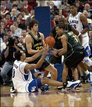 Oregon's Luke Jackson (33) and James Davis, right, battle with former Kansas University player Drew Gooden during the 2002 NCAA Tournament. The Jayhawks won the regional championship game, 104-86, March 24, 2002, in Madison, Wis. Jackson and the Ducks will face the Jayhawks for the third year in a row today at Kemper Arena in Kansas City, Mo.