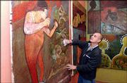 """Cuban-born artist Fito Garche wipes off some of his artwork while setting up his most recent exhibition, """"Memories of Havana,"""" at The Red Dresser, 624 N. Second St. The show will remain on view through December."""