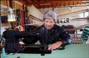 Violet Blowers uses a sewing machine set up in her hangar to make cloth parts for an antique airplane. Blowers has sewn flight jackets for U.S. presidents.