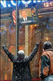 Jeff Gump, of Jacksonville, Fla., raises his arms into the air in a victory gesture in New York as he watches President Bush address the nation after the capture of Saddam Hussein. New Yorkers woke to a new snowstorm Sunday and news that American forces had captured the Iraqi leader in Tikrit.