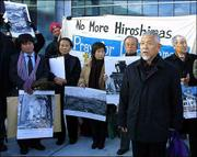 Minoru Nishino, front right, president of a group of Japanese atomic bomb survivors, speaks at a demonstration outside the Smithsonian's new Steven F. Udvar-Hazy Center at Dulles Airport in Chantilly, Va. The group on Monday asked the U.S. government and the Smithsonian Institution to include figures and photographs of Japanese casualties in the new museum exhibit of the Enola Gay, which dropped the first atomic bomb.