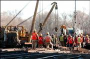 Union Pacific Railroad workers set new sections of track at the site of Wednesday's train derailment in North Lawrence.