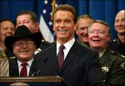California Gov. Arnold Schwarzenegger and law enforcement and government officials laugh at a question from the media after the governor announced that he will invoke emergency powers to order payments to cities and counties without legislative approval during a news conference Thursday in Sacramento, Calif.