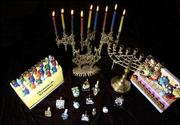 Menorahs, a special candelabrum used during Hanukkah, come in many varieties and can be traditional or fun. Dreidels, a toy similar to a spinning top used in games by children at Hanukkah, are displayed in front.