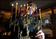 Herb Friedson, a member of the Lawrence Jewish Community Center, lights the menorah, which is used during the celebration of Hanukkah. Eight candles represent the eight days of Hanukkah.