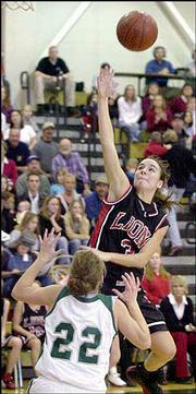 Lawrence High's Drew Huff takes a shot over Free State's Chloe Hall (22) during the Lions' 53-46 victory. LHS won Friday at FSHS.