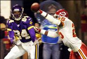 Minnesota wide receiver Randy Moss, left, prepares to catch a 30-yard touchdown pass in front of Kansas City safety Greg Wesley. Moss finished the game with seven catches for 111 yards and two TDs Saturday in Minneapolis.