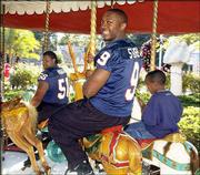 Jayhawks Tony Stubbs (9) and Joe Vaughn go on a merry-go-round ride with children staying at the Give Kids the World Village. Stubbs and Vaughn were among a dozen KU football players -- and coach Mark Mangino -- who visited the resort for children with life-threatening illnesses Sunday south of Orlando, Fla.