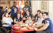 Kansas University quarterback Bill Whittemore and teammates visit with a family at the Give Kids the World village near Orlando, Fla. Players posing with the family Sunday morning while a friend took their photograph were, from left, Whittemore, Tony Stubbs (9), Zach Dyer (13), Joe Vaughn (56), Banks Floodman (5), Kevin Kane (45) and Danny Lewis (78).