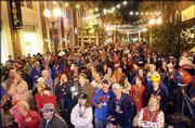 More than 600 Kansas University and North Carolina State fans pack into Wall Street Plaza in downtown Orlando, Fla., for the Tangerine Jam pep rally. Fans participated Sunday in competitions such as yelling and tangerine juice-drinking contests at the pep rally.