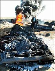 An unidentified Iraqi official of the ministry of oil inspects the scene of a pipeline fire and burned cars near Samarra, 75 miles north of Baghdad, Iraq. Iraqi officials Sunday blamed loyalists of jailed former leader Saddam Hussein for sabotaging a vital stretch of oil pipeline and blowing up a huge gasoline storage tank in Baghdad.