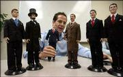 Jesse Combs, president of Toy Presidents Inc., holds a doll of President George W. Bush as he talks about the company's other figures, at the company's Houston headquarters. The other presidents shown are, from left, John F. Kennedy, Abraham Lincoln, Teddy Roosevelt, Bill Clinton and Ronald Reagan. Each presidential doll wears hand-stitched clothing reminiscent of their era, such as Lincoln's top hat and Bush's navy suit, red tie and black cowboy boots adorned with the presidential seal. The dolls also talk; an embedded computer chip plays 25 different phrases the presidents uttered during their administrations.