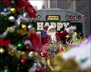 Santa waves from the Holiday Train as it pulls out of downtown Chicago. He and his reindeer ride on a flatbed train car between the commuter train cars.