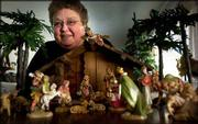 Joan Kogler peers over a Nativity scene she received from her sister. For the past 10 years, the Saline County woman has been collecting the scenes and now has 215 sets and ornaments that she displays in her home during the holiday season.