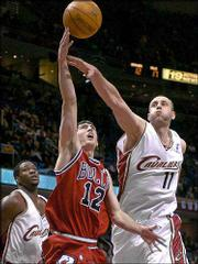 Chicago Bulls' Kirk Hinrich (12) tries to shoot on Cleveland Cavaliers' Zydrunas Ilgauskas (11) as Kedrick Brown, left, watches in the first quarter Friday in Cleveland. Hinrich had 12 points, eight rebounds in six assists in a Chicago victory.
