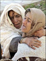 Grieving, injured Iranian women embrace after an earthquake in the Iranian city of Bam, 630 miles southeast of Tehran. The death toll from Friday's quake was at least 5,000.