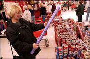 Shirley Wheeler, Lawrence, picks out wrapping paper on sale at SuperTarget in south Lawrence. Shoppers flocked to stores Friday for post-Christmas discounts on seasonal items.