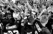 Kansas University football players and fans celebrate after a Jayhawk victory this season. Kansas went from 2-10 in 2002 to a berth in the Tangerine Bowl this year.