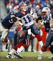 Buffalo quarterback Drew Bledsoe (11) fumbles the ball as he is hit by New England's Teddy Bruschi, left, and Ty Warren, right, during the third quarter. New England won, 31-0, Saturday at Gillette Stadium in Foxboro, Mass.
