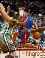 Detroit guard Bob Sura, right, passes behind his back past Atlanta center Theo Ratliff during the first half of Saturday's game in Atlanta. The Pistons won, 87-84.