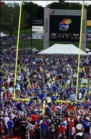 KU football fans climb the north goalpost after KU's win over Missouri in September at Memorial Stadium. Fans ripped down both goalposts before taking them to rest at Potter Lake on campus.