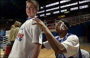 Kansas University basketball player J.R. Giddens signs an autograph for Josh Renne, 13, of Temecula, Calif., during the Holiday Basketball Clinic at Allen Fieldhouse. KU's players shared basketball tips with youths Dec. 27 at the fieldhouse.