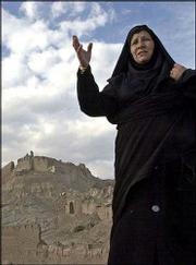 An Iranian woman shares her thoughts after seeing the ruins of Arg-e Bam Citadel, which was the world`s largest mud-brick structure until a Dec. 26 earthquake. Iranian officials plan to rebuild the historic structure, which is seen in the background.