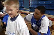 Kansas University basketball player Wayne Simien signs an autograph for Harry Brewer, 10, of Gladstone, Mo., during the team's Holiday Basketball Clinic at Allen Fieldhouse. Youngsters got a chance to learn from KU players and coaches during the Dec. 27 clinic.