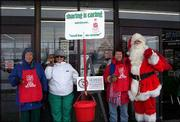 From left, Jean Lominska, Shirley Halladay, Lori Michel and Larry Kline, as Santa, volunteer their time to be bell ringers for the Salvation Army. The members of Altrusa International of Lawrence rang the bells Dec. 13 at Checkers Foods, 2300 La.